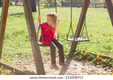 Little girl on swing in the park. Autumn season.