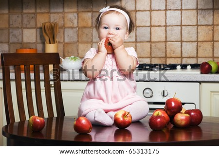 Little girl on table at kitchen eating an apple - stock photo