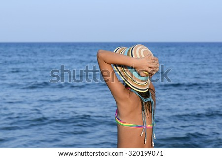 Little girl on the beach at sunset portrait with her hands blocking the large hat - stock photo