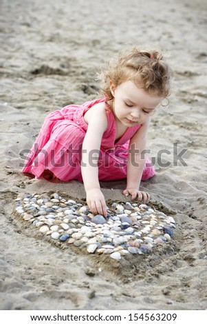 Little girl on the beach playing with shells