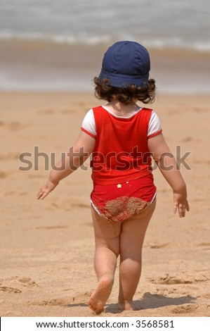 little girl on the beach running to the water