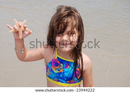 Little girl on the beach with a starfish - stock photo