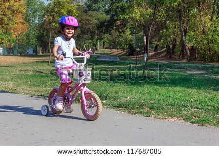 Little girl on the bicycle - stock photo
