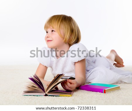 little girl on the floor studying with books and paper - stock photo