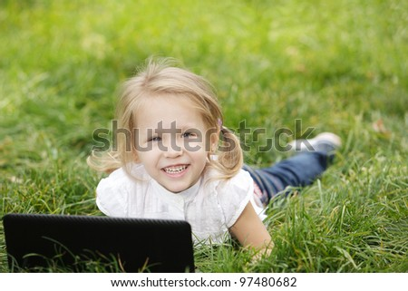 Little girl on the grass with laptop - stock photo