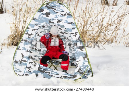Little girl on the ice fishing in the tent - stock photo