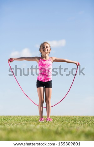 Little girl on the nature of the jumps with a skipping rope - stock photo