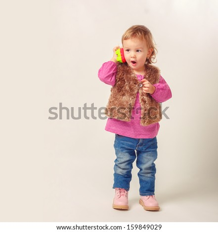 Little girl on the phone isolated on cream-colored