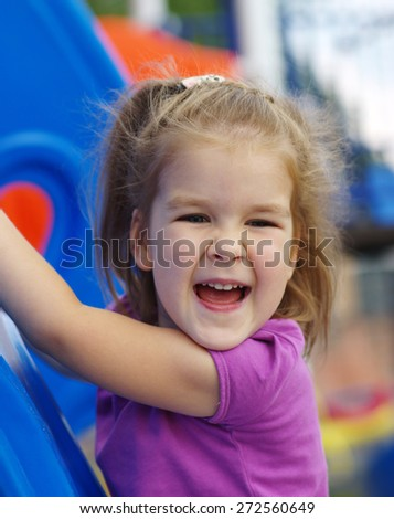 little girl on the playground. Happy smiling child playing on outdoor. - stock photo