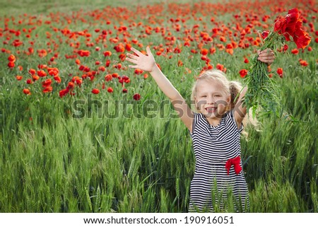 Little girl on the poppy meadow greeting happy with hands outspread - stock photo