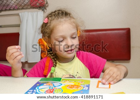 Little girl on the train sits at a table on the lower second-class place car and enthusiastically skin application