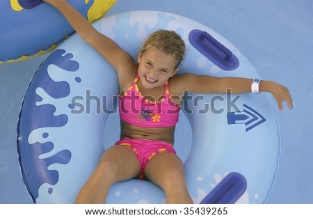 little girl on tube in pool - stock photo