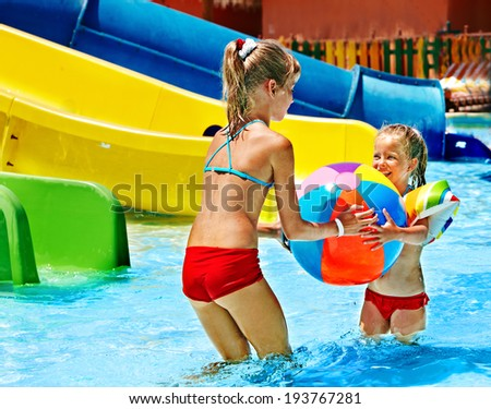 Little girl on water slide at aquapark. - stock photo