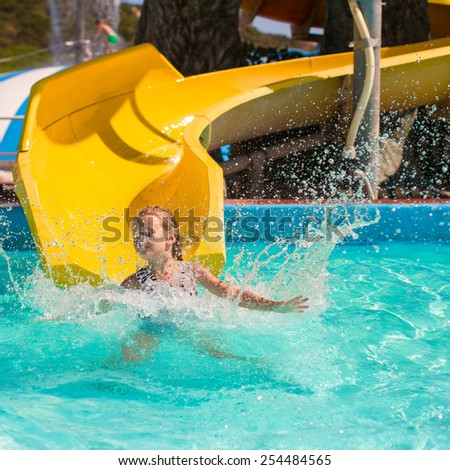 Little girl on water slide at aquapark during summer holiday - stock photo