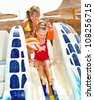 Little girl on water slide at aquapark. Summer holiday. - stock photo