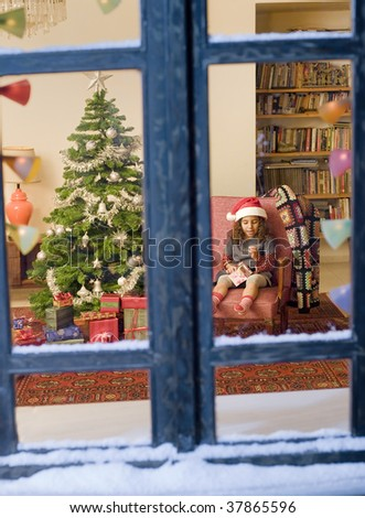 little girl opening a Christmas present watched from a snowy window