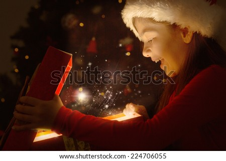 Little girl opening a magical christmas gift against snow - stock photo