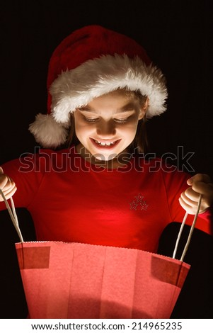Little girl opening a magical christmas gift on black background - stock photo