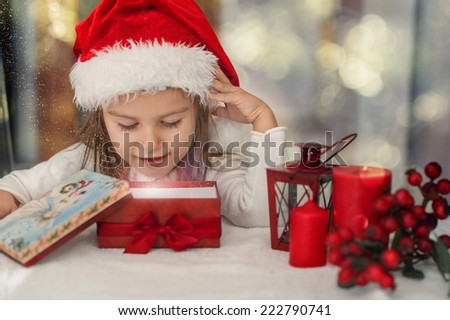 Little girl opening at present box. Magic shining gift - stock photo