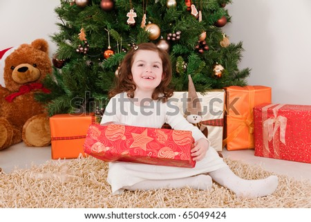 Little girl opening Christmas-boxes - stock photo