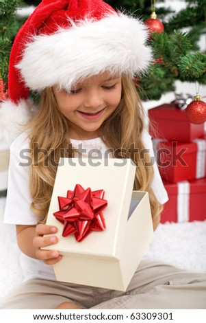 Little girl opening present in front of christmas tree - closeup - stock photo