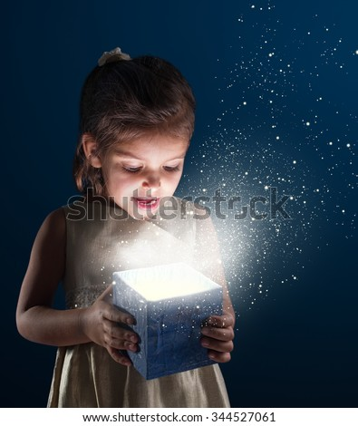 Little girl opens a gift. It is lit from within. Dark - blue background. - stock photo