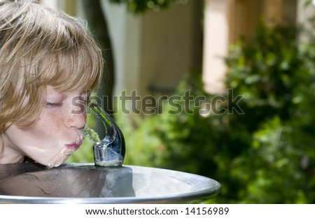 Little Girl (or Boy) slurping at the Drinking Fountain - stock photo