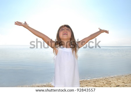 Little girl outdoor standing with her hand outstretched - stock photo