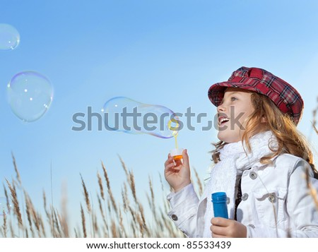 little girl outdoors blowing soap bubbles - stock photo