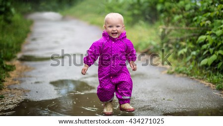 Little girl outdoors standing in a puddle