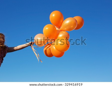 little girl outdoors with balloons - stock photo