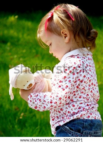 Little girl outside in the park  with her teddy bear. - stock photo