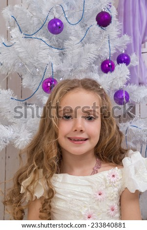 Little girl over christmas fir tree with wicker basket of presents - stock photo