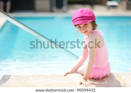 Little girl paddling her feet in a swimming pool while looking back to the camera - stock photo