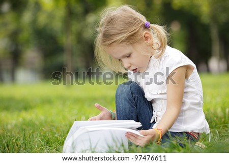 Little girl paging the book outdoors - stock photo