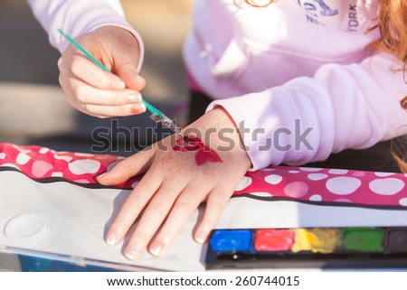 Little girl paining hearts on her hand. - stock photo