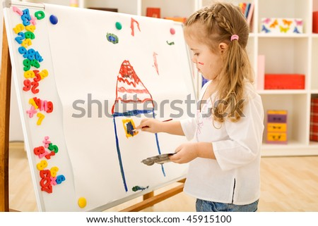 Little girl painting a colorful house on a large paper