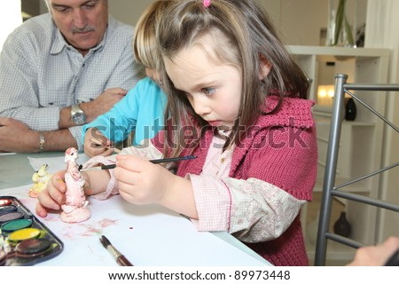 Little girl painting a figurine - stock photo