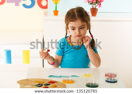 little girl painting a picture