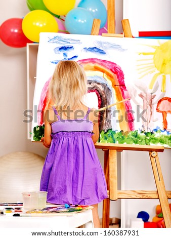 Little girl painting at easel in school. - stock photo