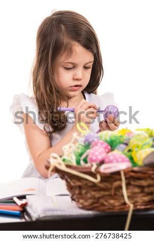 Little girl painting Easter egg against white background - stock photo