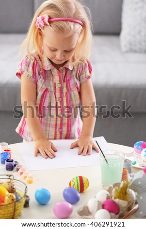 Little girl painting Easter eggs, indoors