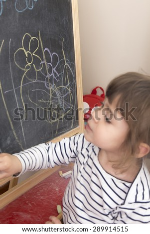 Little girl painting flowers on blackboard.