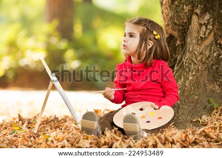 Little girl painting in a park - stock photo