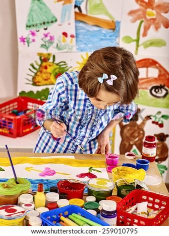 Little girl painting  in school. Girl short hair. - stock photo