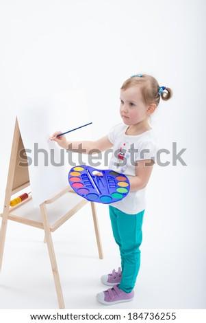Little girl painting on easel - stock photo