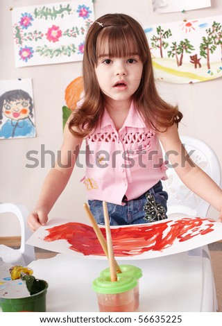 Little girl painting picture in art class.
