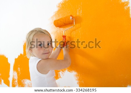 Little girl painting white wall with orange color - stock photo