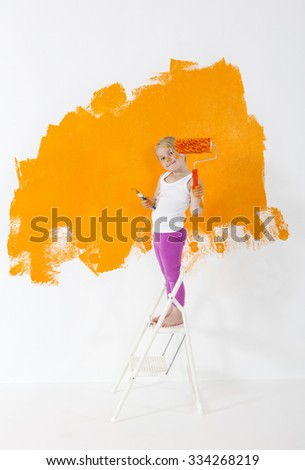 Little girl painting white wall with orange color