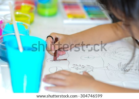 little girl painting with crayon color - stock photo